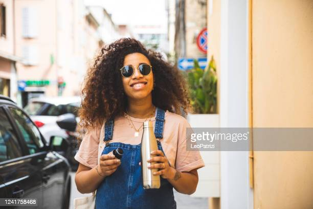 portrait of a smiling afro hair woman holding a reusable water bottle - reusable stock pictures, royalty-free photos & images