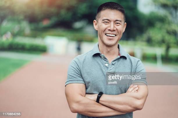 笑顔のアジアの民族の男の肖像 - ポロシャツ ストックフォトと画像