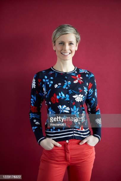 portrait of a smiling blond woman - hände in den taschen stock-fotos und bilder