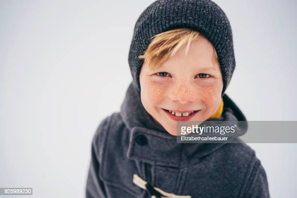 Portrait of a smiling boy holding a Christmas wreath