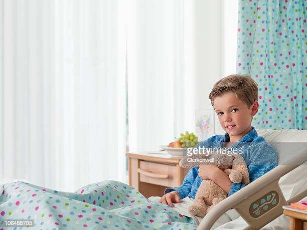 Portrait of a smiling boy (10-11) holding teddy bear in hospital bed