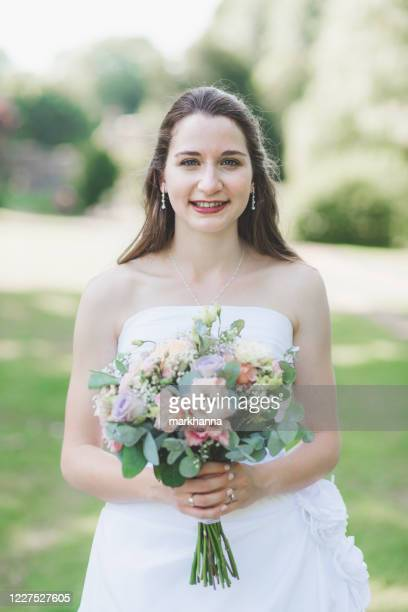 portrait of a smiling bride holding a wedding bouquet - strapless stock pictures, royalty-free photos & images
