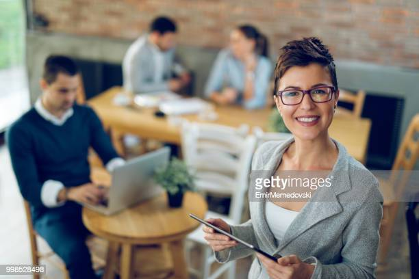 Portrait of a smiling business woman holding digital tablet
