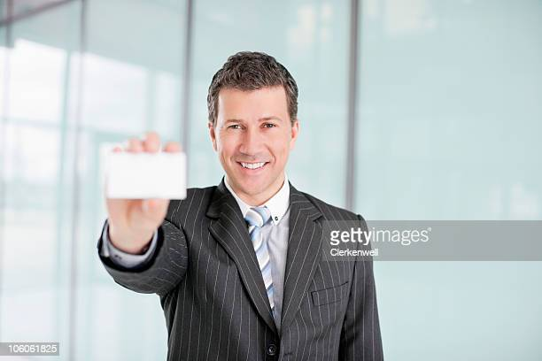 Portrait of a smiling businessman showing blank business card