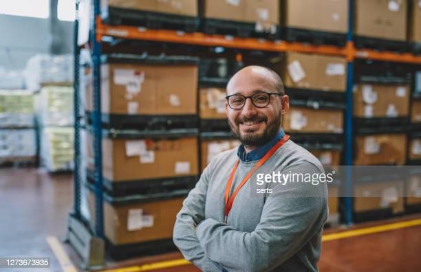 portret van een glimlachende zakenman die zich in gang van pakhuis bevindt - mid volwassen stockfoto's en -beelden