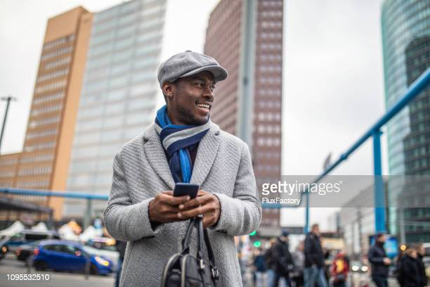 portrait of a smiling businessman using his smartphone - black hat stock pictures, royalty-free photos & images