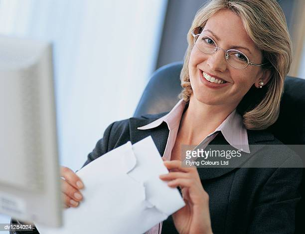 Portrait of a Smiling Businesswoman Opening Her Mail at Her Desk