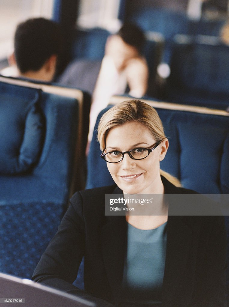 Portrait of a Smiling Businesswoman Sitting on a Passenger Train : Stock Photo