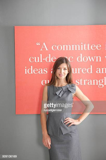 Portrait of a smiling businesswoman standing in office in front of inspirational quote