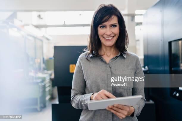 portrait of a smiling businesswoman using a tablet in a factory - braunes haar stock-fotos und bilder