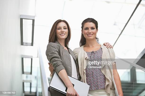 Portrait d'un souriant femmes debout avec les bras autour