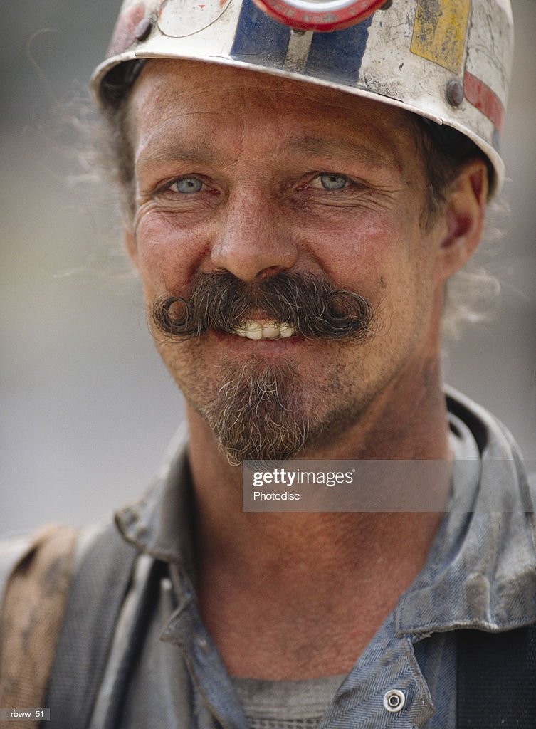 portrait of a smiling caucasian miner in a hardhat : Foto de stock