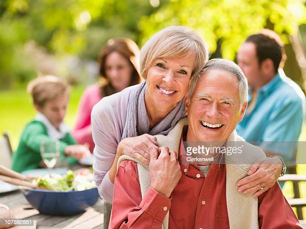 Portrait of a smiling couple on picnic with people in background