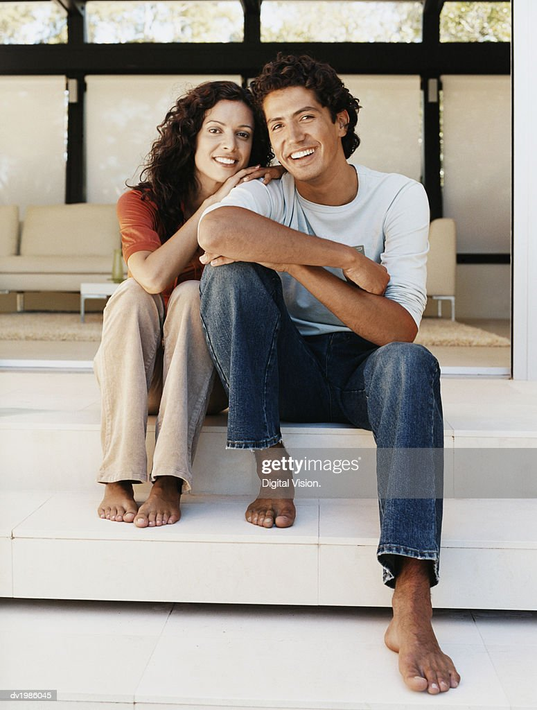 Portrait of a Smiling Couple Sitting Together on a Patio : Stock Photo