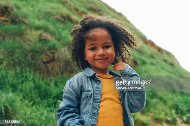 portrait of a smiling dark curly-haired girl. - primary age child stock pictures, royalty-free photos & images