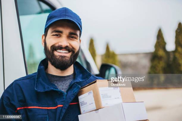 portrait of a smiling deliverer - post office stock pictures, royalty-free photos & images