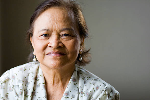 portrait of a smiling elderly asian woman against gray back - old asian woman filipina stock pictures, royalty-free photos & images