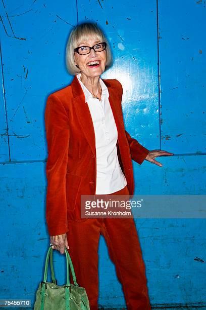 Portrait of a smiling elderly Scandinavian woman in a red suit.