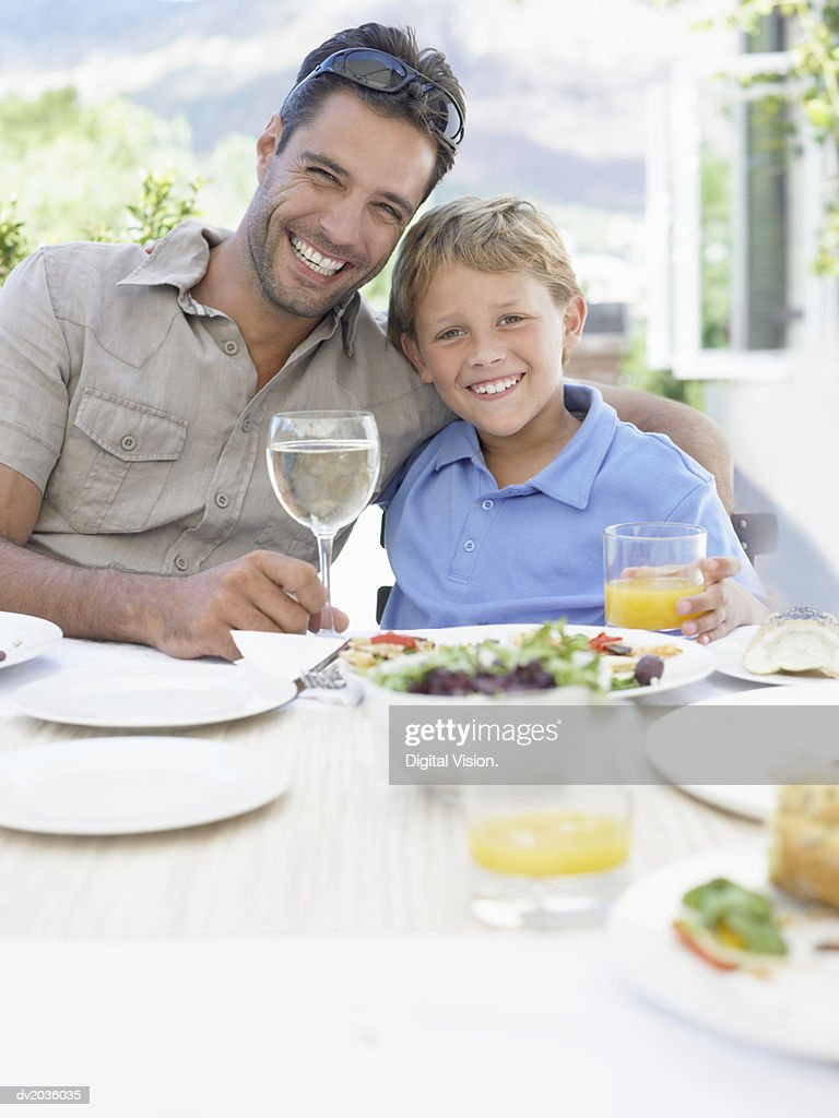 Portrait of a Smiling Father Sitting With His Son at a Dinner Table Outdoors : Stock Photo