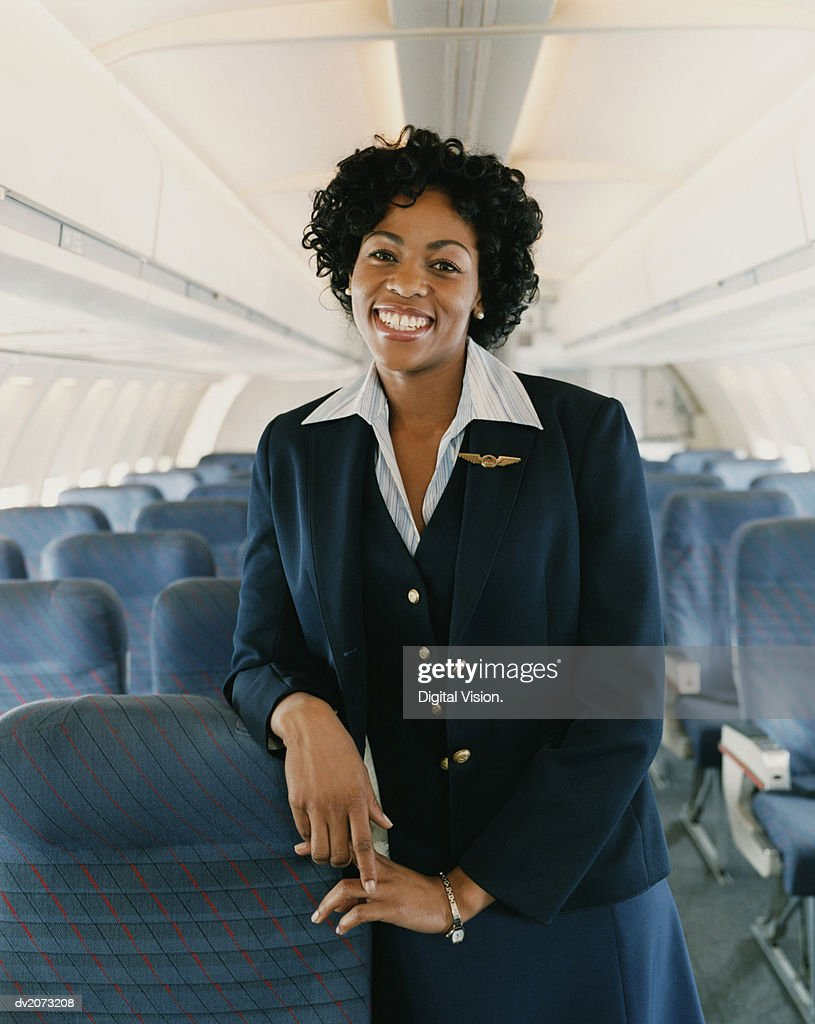 Portrait of a Smiling Female Flight Attendant on a Plane : Stock Photo