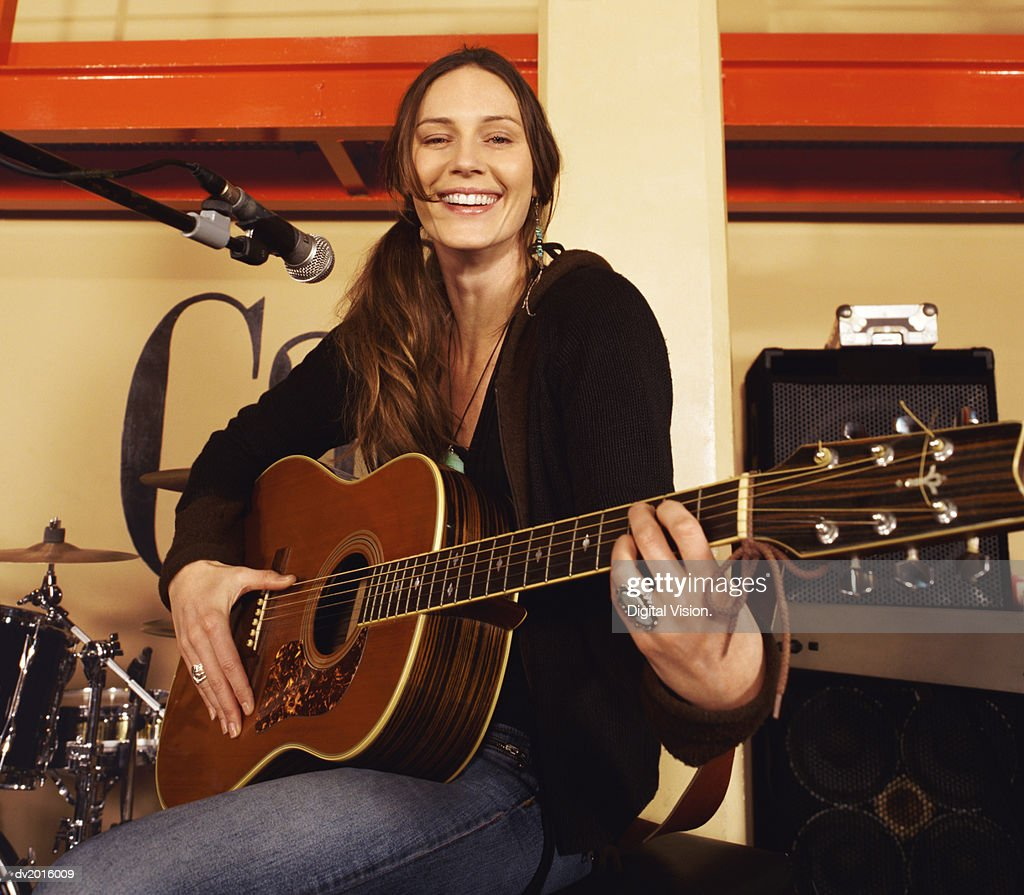 Portrait of a Smiling Female Guitarist Sitting on a Stage by a Microphone Stand : Stock Photo