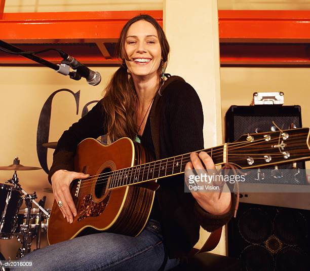portrait of a smiling female guitarist sitting on a stage by a microphone stand - pop musician stock photos and pictures