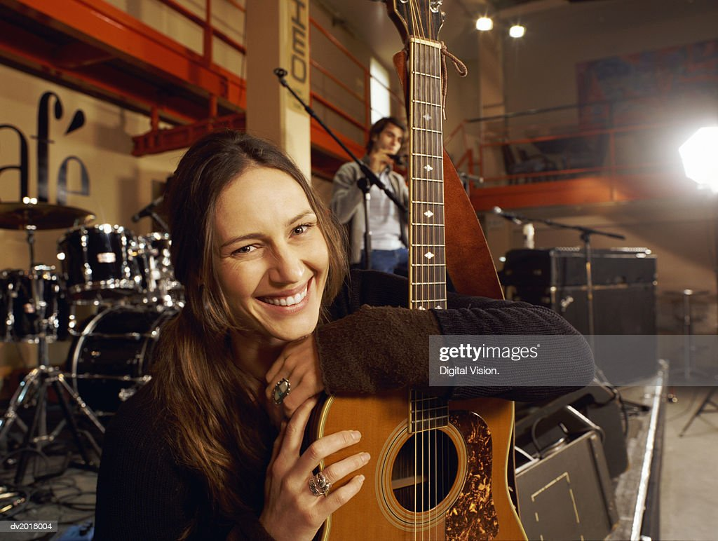 Portrait of a Smiling Female Guitarist Sitting on a Stage in a Bar : Stock Photo