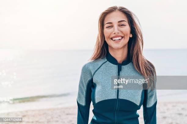 Porträtt av en leende kvinnliga surfare