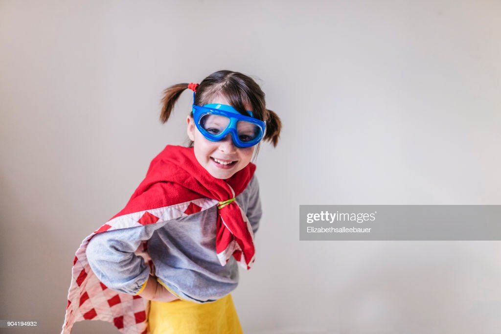 Portrait of a smiling girl dressed as a superhero : Stock Photo