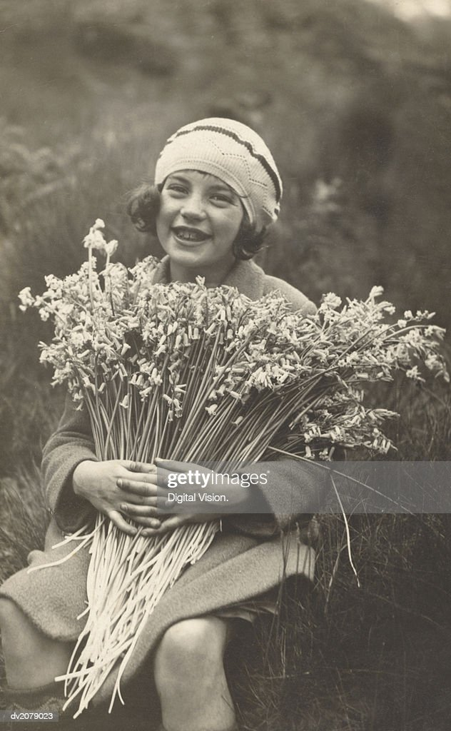 Portrait of a Smiling Girl Holding a Bunch of Flowers : Stock Photo