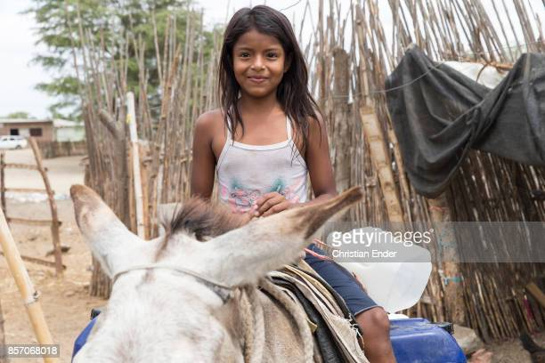 Portrait of a smiling girl riding on a donkey in front of a wooden fence carrying an empty water bottle near Sullana Peru