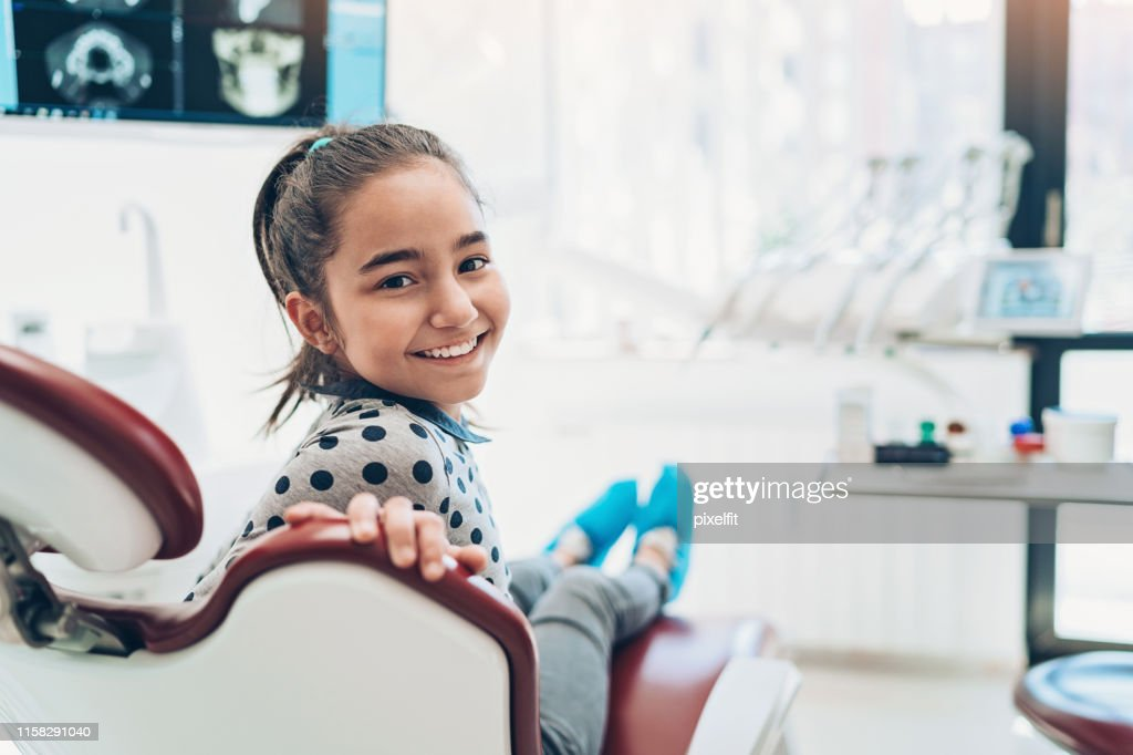 Portrait of a smiling girl sitting on a dentist's chair : Stock Photo