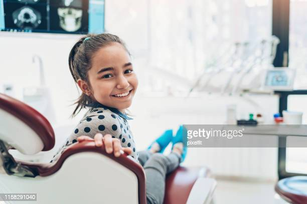 portrait of a smiling girl sitting on a dentist's chair - dentist stock pictures, royalty-free photos & images