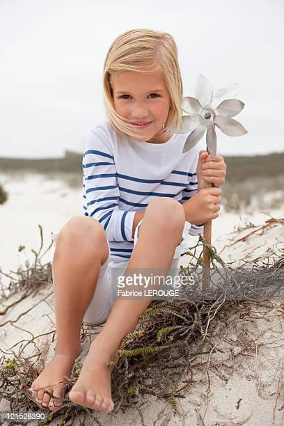 Portrait of a smiling girl sitting on sand and holding pinwheel
