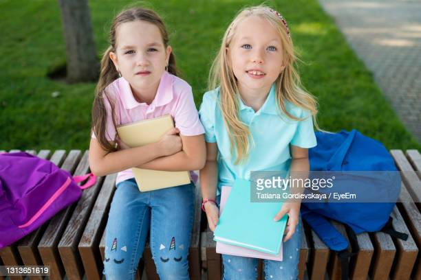 portrait of a smiling girl sitting outdoors - tag 1 stock-fotos und bilder