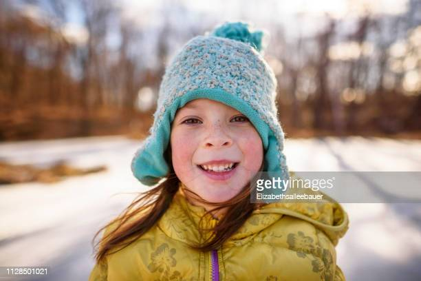 portrait of a smiling girl standing by a frozen pond, united states - nur kinder stock-fotos und bilder