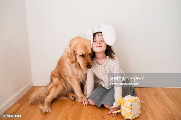 portrait of a smiling girl wearing bunny ears sitting on the floor with her dog - dog easter stock pictures, royalty-free photos & images