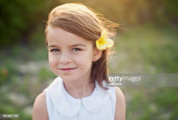 portrait of a smiling girl with a flower in her hair - 6 7 jahre stock-fotos und bilder