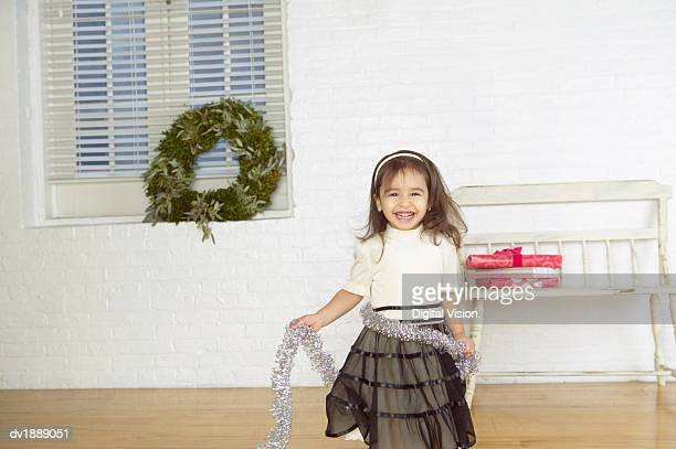 Portrait of a Smiling Girl Wrapped in Tinsel
