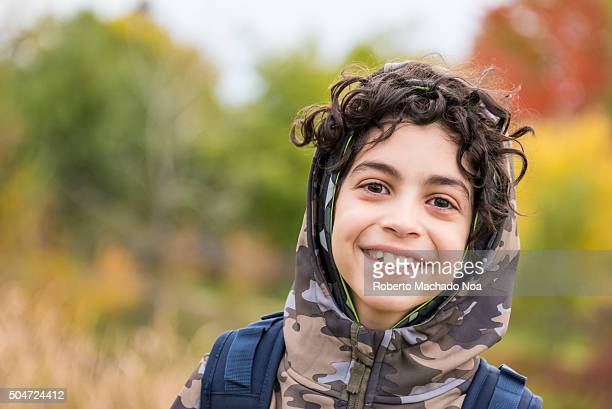 Portrait of a smiling happy boy with curly hair having fun in Winter against autumn background