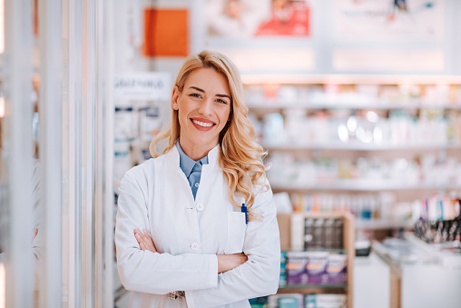 Portrait of a smiling healthcare worker in modern pharmacy. 1133588480