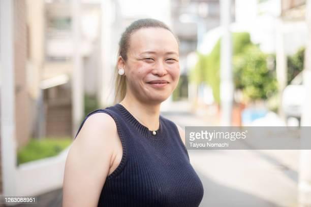 portrait of a smiling japanese woman on the street - ポジティブなボディイメージ ストックフォトと画像