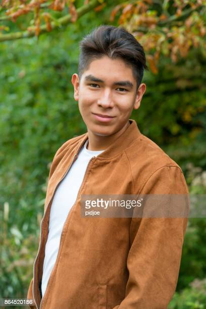 portrait of a smiling  latin american young man with a brown suede jacket, shot outside - handsome native american men stock pictures, royalty-free photos & images