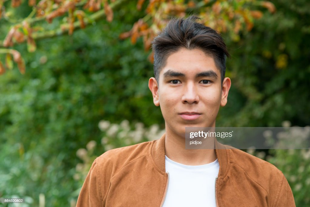 Portrait of a smiling  Latin American young man with a brown suede jacket, shot outside : Stock Photo