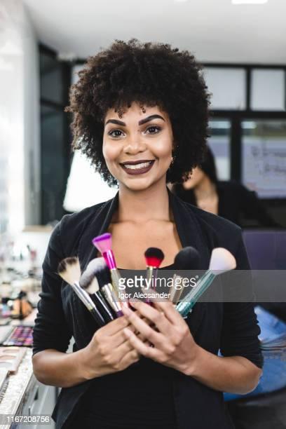 portret van een lachende make-up artiest houden borstels - visagist stockfoto's en -beelden