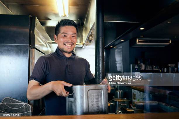 portrait of a smiling male chef standing in a commercial kitchen - chigasaki stock pictures, royalty-free photos & images