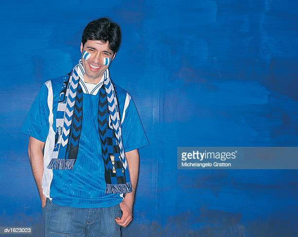 Portrait of a Smiling, Male Football Supporter Standing by a Blue Wall With His Hand in His Pocket