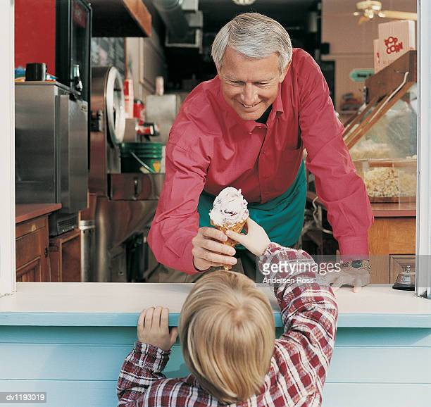 Portrait of a Smiling Man Giving an Ice Cream Cone to a Young Child From an Ice Cream Stand