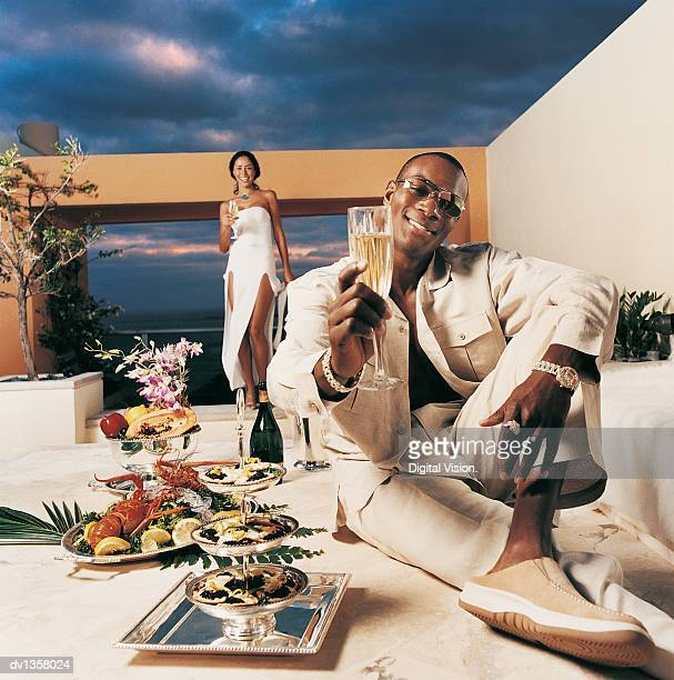 Portrait of a Smiling Man Holding a Glass of Champagne and Sitting in a Courtyard by Trays of Seafood With a Woman Standing in the Background