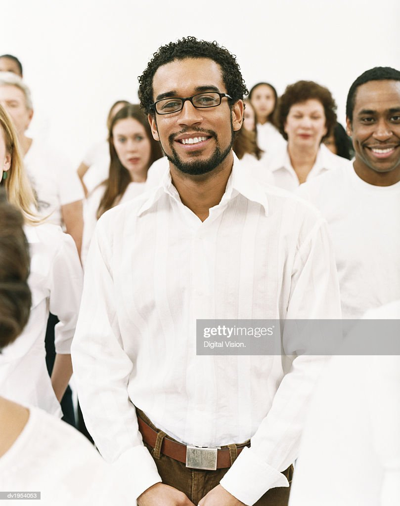 Portrait of a Smiling Man in a White Shirt Standing in a Crowd : Stock Photo